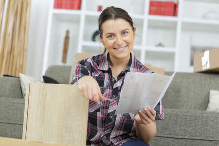 Woman reading instructions for assembling furniture Imagens