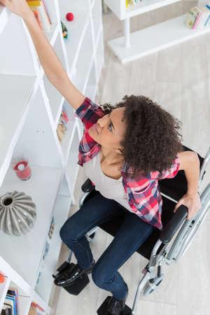 Femme en fauteuil roulant en essayant de quelque chose de la étagère Banque d'images - 86844008