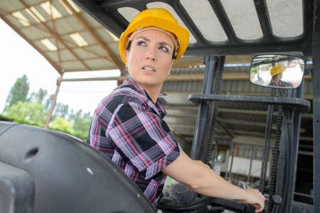 reversing: Woman reversing forklift truck