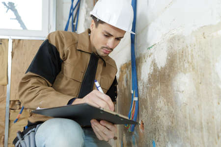 Workman making notes on clipboard Stock Photo
