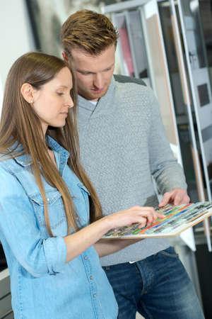 젊은 부부는 안내 책자를 함께 연구합니다. 스톡 콘텐츠