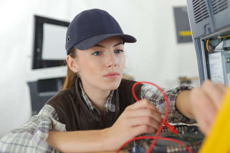 woman handle success: woman checking the voltage of a machine