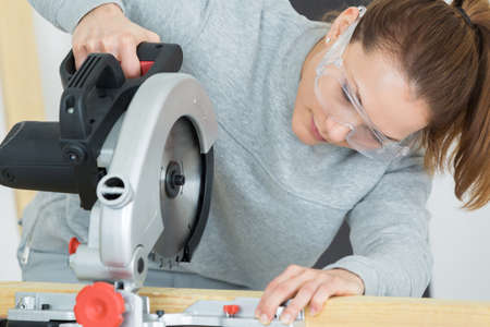 young female carpenter is using a circular saw
