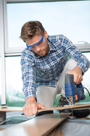 young man carpenter builder working with electric jigsaw and wood Stock Photo