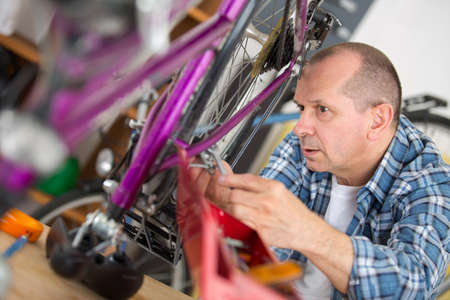 mechanic setting up chain on bicycle in workshop Imagens - 86906403