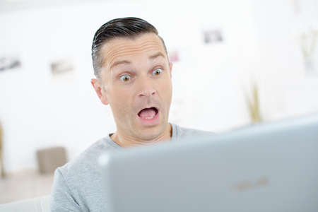 shocked businessman working on computer in his office