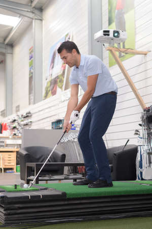 golfer practicing indoors Stock Photo