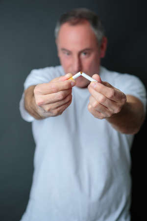 man breaking cigarette as a gesture of quitting smoking