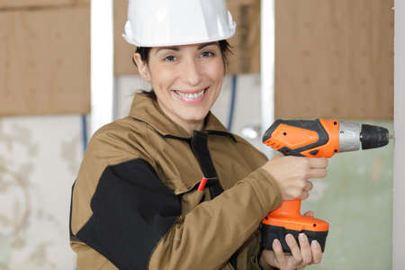 female carpenter at work using hand drilling machine Stock Photo
