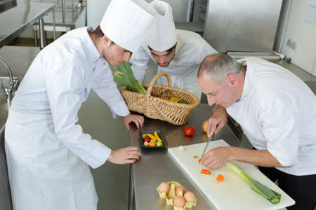 head-chef teaching colleagues how to slice vegetables in kitchen Stock Photo