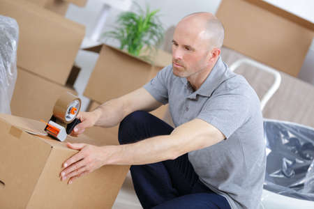man closing boxes to move into new home