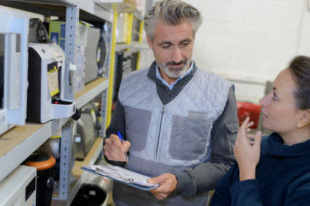 manager showing clipboard to worker in warehouse Stock Photo