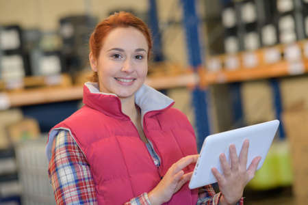 pretty young female with tablet against forklift in large warehouse Stock Photo