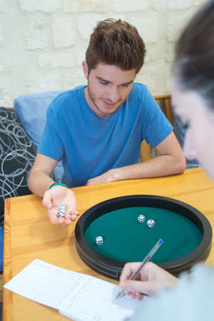 young couple playing five dice game