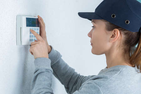 female worker entering code on electronic keypad on wall Stock Photo