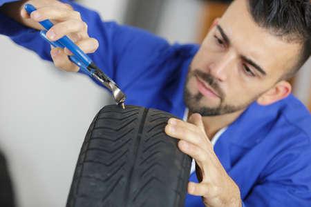 자동차 정비사가 발톱으로 타이어를 못쓰게하다. 스톡 콘텐츠 - 87683279