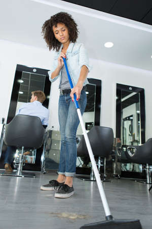 smiling hairstylist sweeping hair clippings on floor in her salon