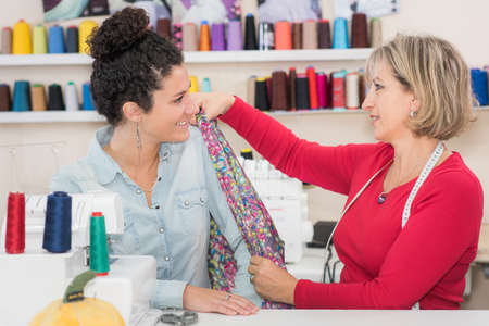tailor taking shoulder measurement of a lady customer Stock Photo