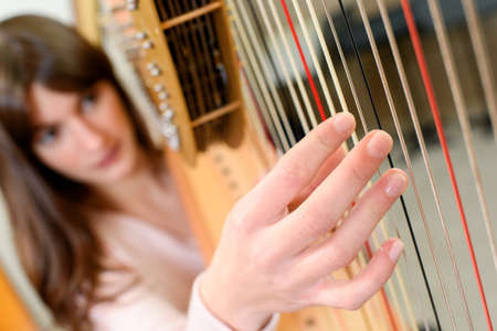 girl playing a harp Stock Photo