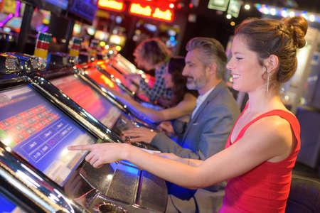 gelukkige vrouw zitten op gokautomaat in casino salon