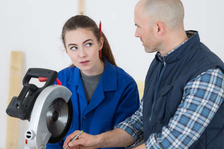 young female apprentice being introduced to a circular saw