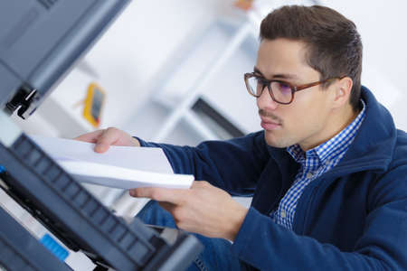 man putting paper sheet into printer tray
