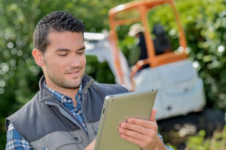 Man looking at tablet, digger working in background
