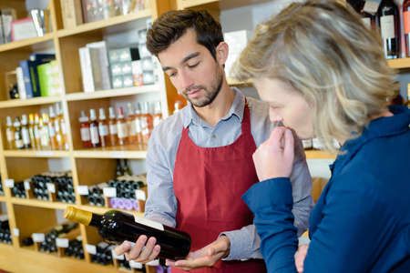 woman choosing bottle of wine in shop with alcohol beverages