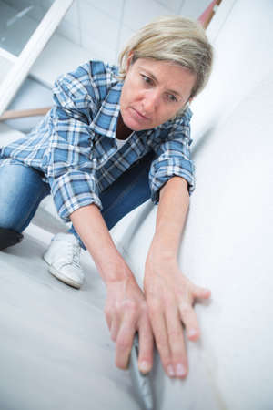 handywoman: handywoman laying fitted carpet