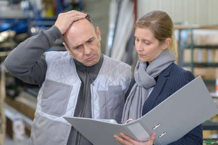 man frowning while looking at folder held by woman Stock Photo