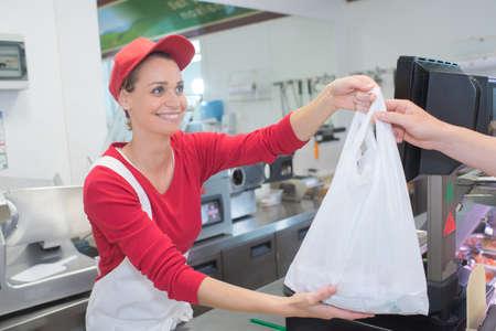 ショップのカウンターでお客様に袋を与える女性の肉屋 写真素材