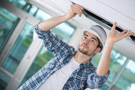 contractor replacing overhead ceiling panel