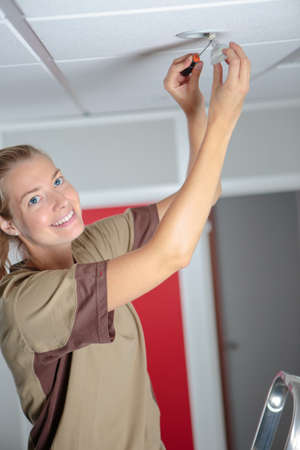vrouw op ladder gloeilamp in nieuw huis te passen
