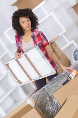 Mujer sosteniendo pintura y rodeado de cajas Foto de archivo - 87722883