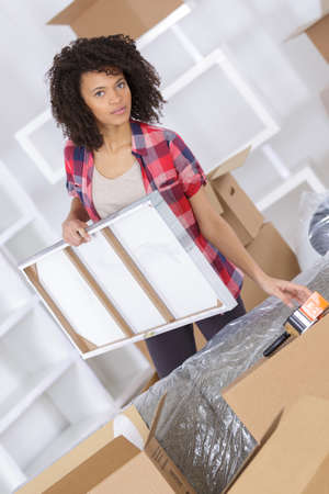 woman holding painting and surrounded by boxes Stock Photo