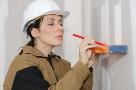 여자가 벽에 직선을 표시하는 작업 바지에 스톡 콘텐츠