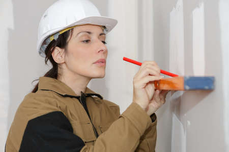 woman in overalls marking straight line on a wall
