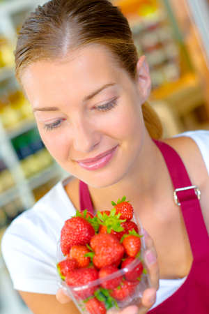 Woman looking at strawberries Stock Photo
