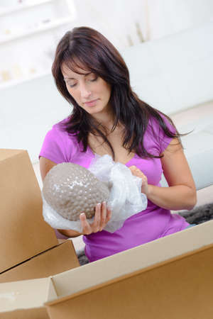 woman packing decorative buddha for relocation