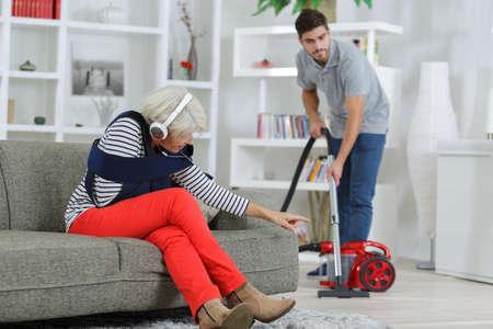 senior injured woman asking young man home help something Standard-Bild