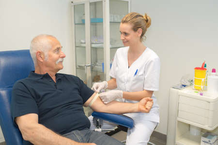 phlebotomist: female doctor collecting patients blood for test