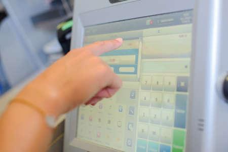 shop-assistants hand pressing a screen cash register in a shop Stock Photo