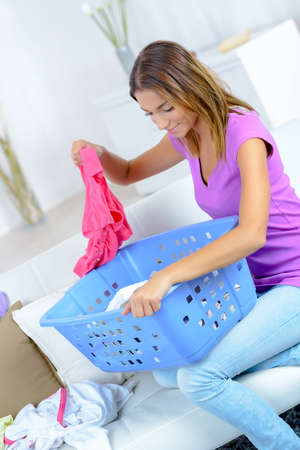 young happy woman laundering clothes at home