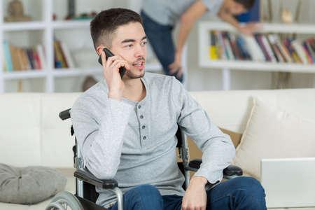휴대 전화를 사용하여 휠체어에 소년
