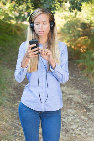 young woman listening to music on a smart phone outdoors Stock Photo