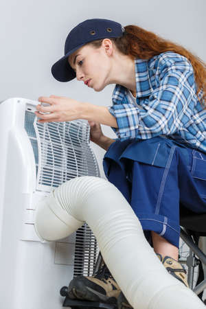 female operator inspecting heating ventilated and air conditioning Stock Photo
