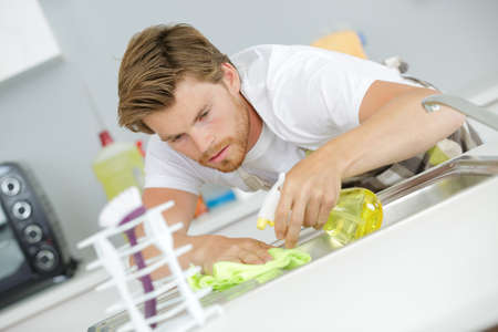 man cleaning a sink Stock Photo