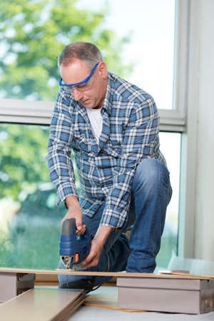 man carpenter builder working with electric jigsaw and wood Stock Photo