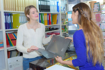 Woman looking at folder in stationery shop Stock Photo