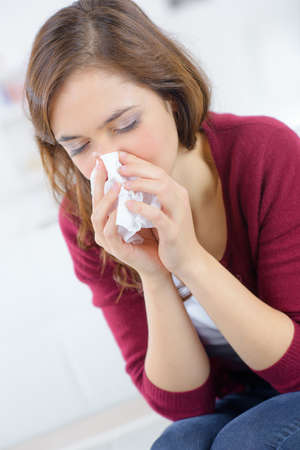 unhappy woman with paper napkin blowing nose Stock Photo